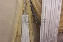 Кисть кипельно белого цвета с шаром из страз, добавляет простой ткани Kresh дороговизны и завершает шторную композицию.
